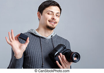 young smilling photographer in shirt  holds the battery for DSLR