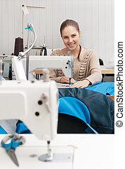 young smilling seamstress at work - young seamstress at work
