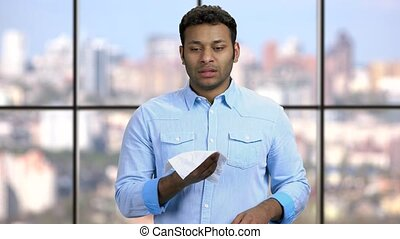 Young sneezing man catch a cold. Indian man holding tissue and sneezing on checkered window background.