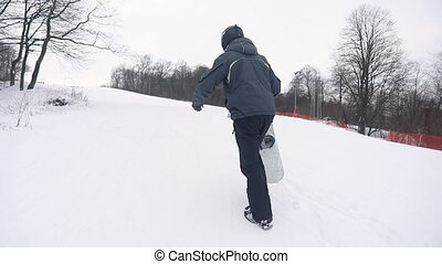 Snowboarder Climbing the Mountain for Skiing - Young...