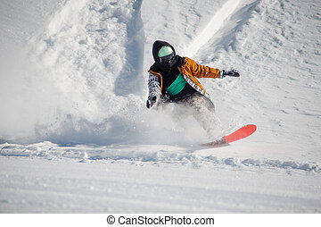 Young snowboarder in colorful sportswear riding with snowboard down powder snow hill