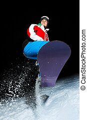 Young snowboarder jumping at night