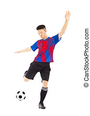 Young soccer player kicking ball