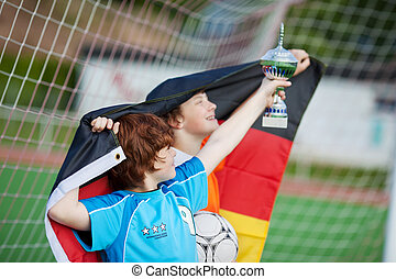 young soccer players with trophy and flag