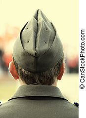 young soldier in field cap focusing point on back of the head