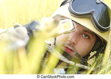 Young soldier in helmet targeting