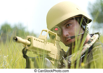 Young soldier in helmet targeting