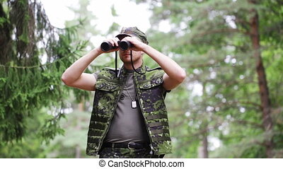 young soldier or hunter with binocular in forest - hunting,...