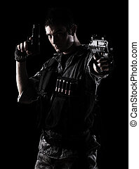 young soldier shooting with a pistol on a black background