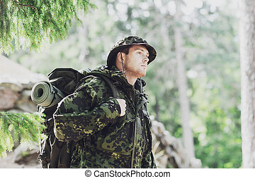 young soldier with backpack in forest - war, hiking, army ...