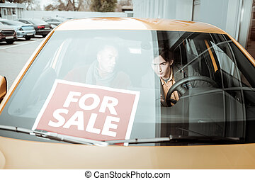 Young son and his caring father sitting in orange car for sale