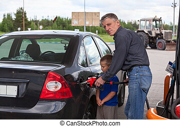 Young son looking at father refilling car at gas station