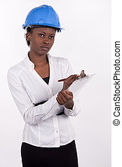 Young South African woman wearing a hard-hat, and making notes on a pad.