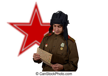 young Soviet tanker look at a map,he have a tank helmet
