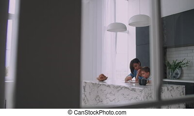 Young Spanish mother and son sitting at the table reading a...