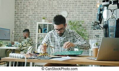 Young specialist is making motherboard for robot using soldering iron in office, hus African American colleague is using computer in background. People and job concept.
