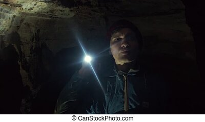 Young Speleologist standing in narrow cave with flashlight...