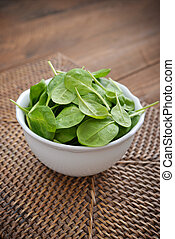 Young spinach in a white bowl on wooden background