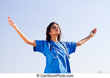 young spiritual nurse on beach on blue background