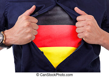 Young sport fan opening his shirt and showing the flag his country germany, german flag