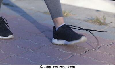 Young sport woman tying running shoes during training outside