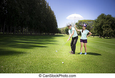Young sportive couple playing golf