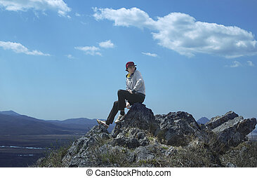 Young sportive man in red cap sit