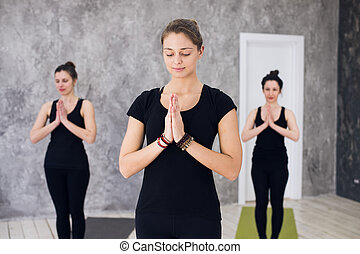 Young sportive trio group of girls are practicing yoga exercises in the studio