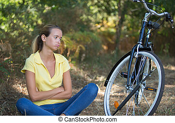 young sportive woman with broken bike in the forest