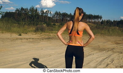 young sports girl in tight clothes walks outdoors - pretty...