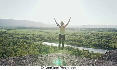 Young sports girl standing on top of the high cliff above the river at beautiful golden sunset, raising her hands up in the air cheerfully jumps up. The athletic young womanl is standing on the top of the mountains