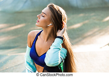 Young sports lady in park outdoors listening music with earphones.