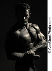 Young sports male with a naked torso against a dark background. Monochrome photos athlete
