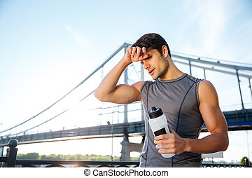 Young sports man resting after running and holding water bottle