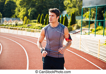 Young sports man running down stadium track with earphones