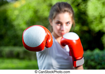 Young sports woman boxing with gloves to the camera in the park