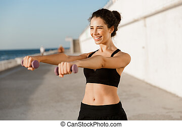 Young sports woman make exercises with dumbbells outdoors on the beach.