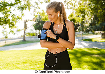 Young sports woman outdoors on grass using mobile phone listening music.