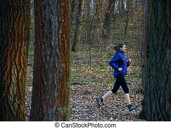 Young Sports Woman Running on the Trail in the Wild Forest Among Big Trees
