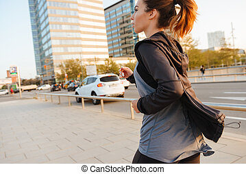 Young sports woman running outdoors on the street.