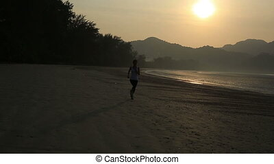 young sports woman running on sunrise seaside beach