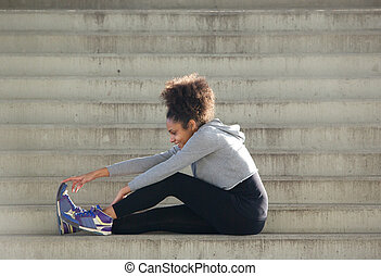 Young sports woman sitting on stairs stretching leg muscles
