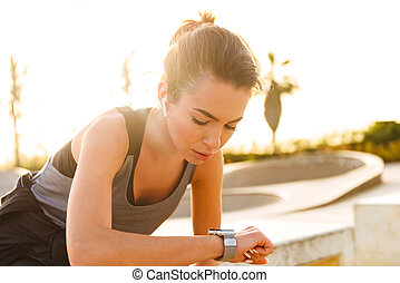 Young sports woman sitting outdoors listening music