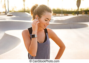 Young sports woman standing outdoors listening music