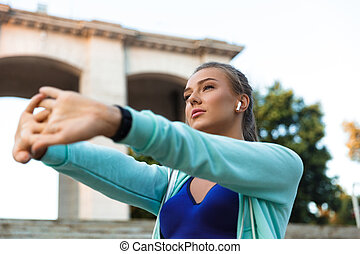 Young sports woman standing outdoors make stretching exercises listening music with earphones.