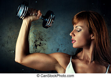 Young sports woman with dumbbell portrait.