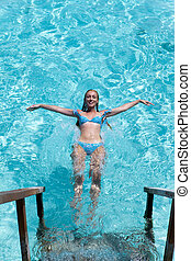 Young sports woman swims from steps