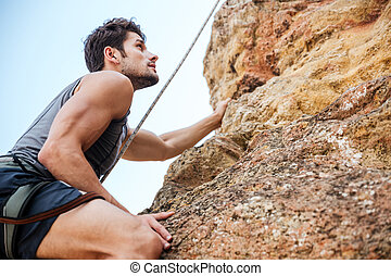 Young sportsman climbing up a rock cliff
