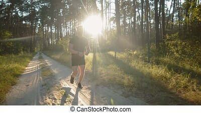Full length portrait of young sportsman in black t-shirt and shorts doing evening cardio at green forest. Handsome man training on nature during amazing sunset.
