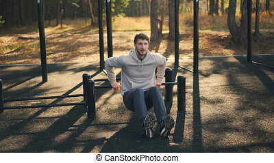 Young sportsman is doing sports outdoors in park...